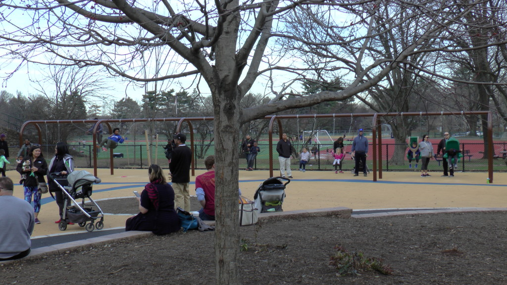 View of Swings via Central area in middle of playground